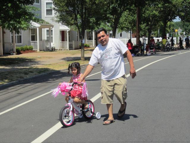 Latino man and child on training bike