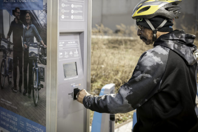 man using bike share kiosk