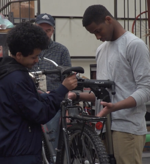 Two young men work together to fix a bicycle.