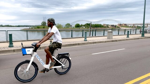A man rides his bike down an open street