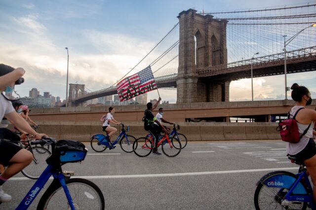"People on bikes ride across a bridge, and one person holds up an American Flag with the words ""I can't breathe"" written on it."
