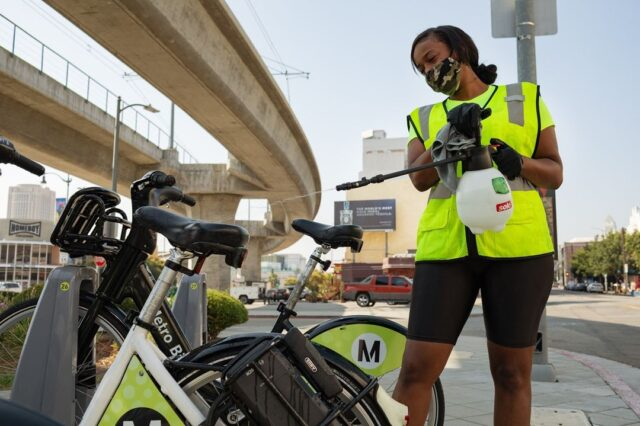 A brown, female Metro Bike Share employee cleans bikes while wearing a mask.