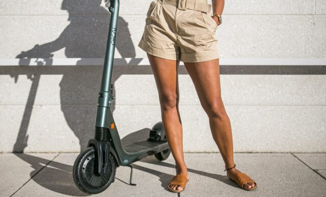 Bottom half of woman is cropped standing next to an e-scooter.